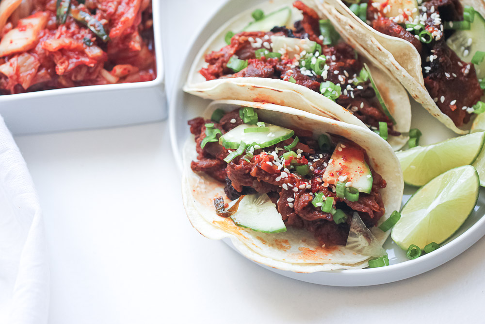 Juicy, sweet and spicy Korean pork tacos topped with fresh kimchi and the most finger licking good gochujang sauce all on a tortilla. Make the best tacos of your life!